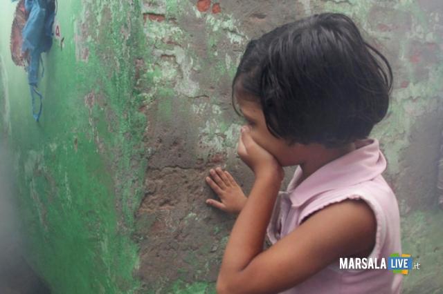 Una bambina si copre il volto con la mano in una foto d'archivio. ANSA/PIYAL ADHIKARY